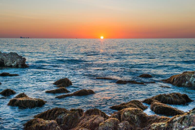Paesaggio di tramonto con il sole dorato e pietre in mare immagini stock libere da diritti