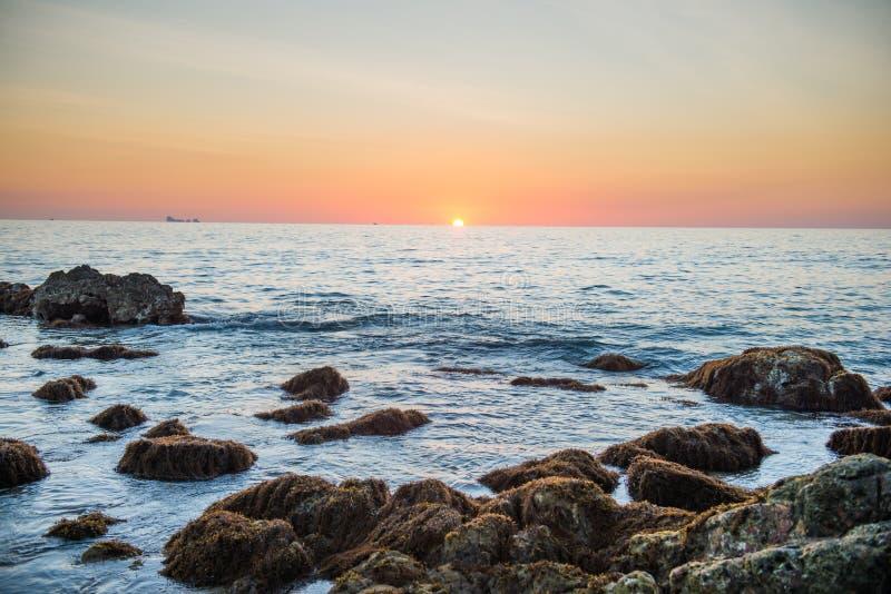 Paesaggio di tramonto con il sole dorato e pietre in mare immagine stock libera da diritti