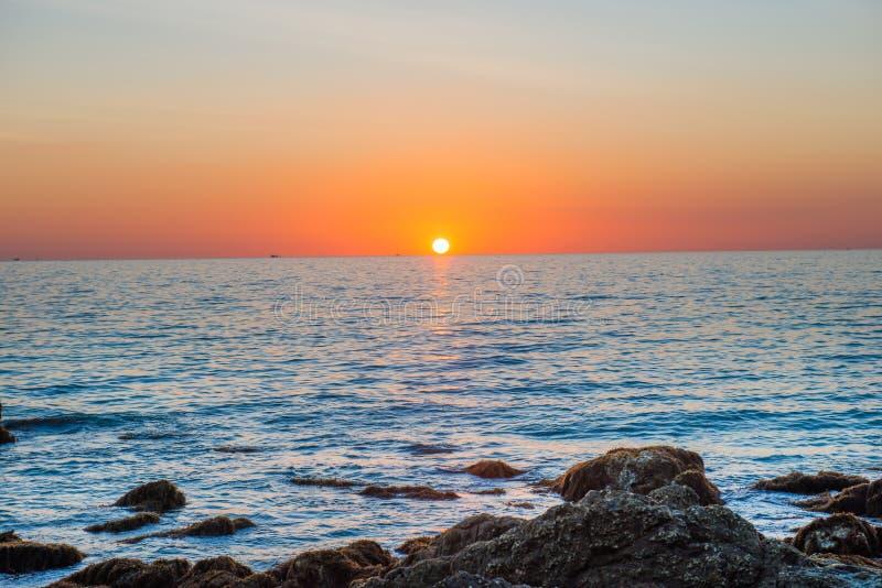 Paesaggio di tramonto con il sole dorato e pietre in mare fotografia stock