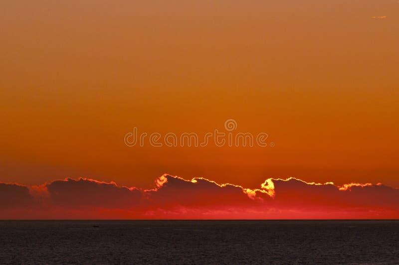 Paesaggio di tramonto con l'oceano e le nuvole fotografia stock