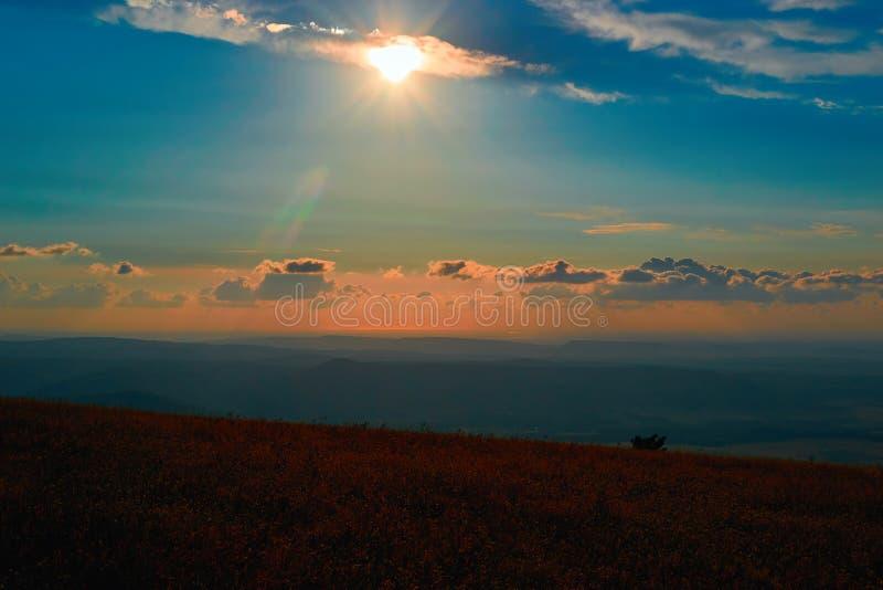 Paesaggio di tramonto di sera sopra la valle della montagna Il sole e l'arancia luminosi di sera si rannuvola le montagne basse,  fotografia stock libera da diritti