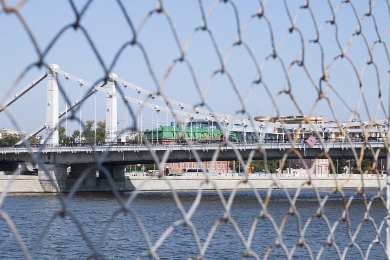 Paesaggio di un ponte sospeso sopra il fiume di Moskva Una vista da dietro la griglia fotografia stock libera da diritti