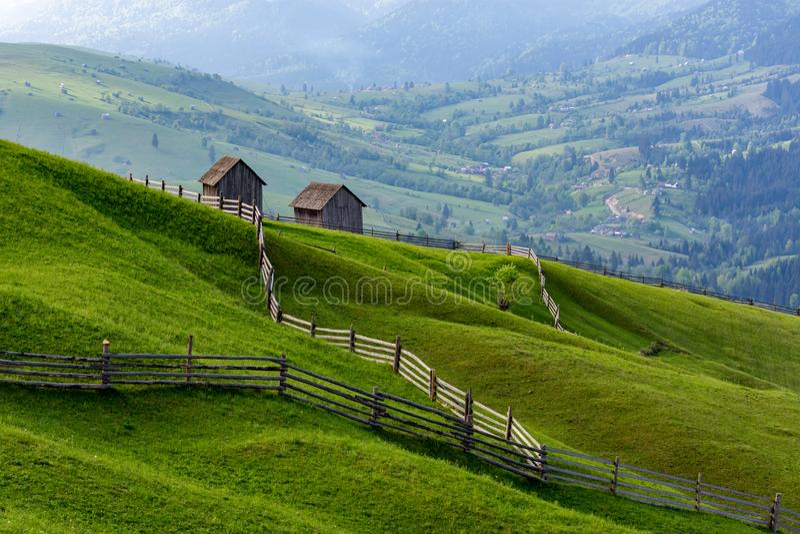 Paesaggio di un prato verde crudo con le linee principali ai granai, Bucovina, Romania fotografia stock libera da diritti