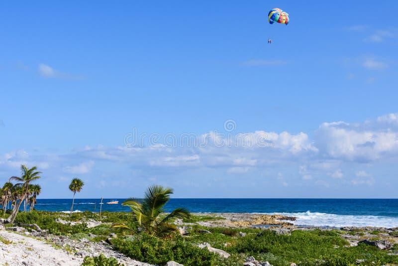Paesaggio di una spiaggia tropicale con le palme Parasailing dei turisti in un cielo blu fotografie stock