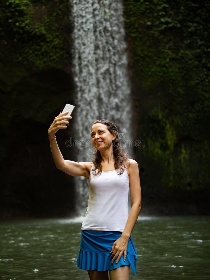 Paesaggio enjoing della cascata della donna caucasica felice, facente selfie con lo smartphone vicino alla cascata fotografia stock