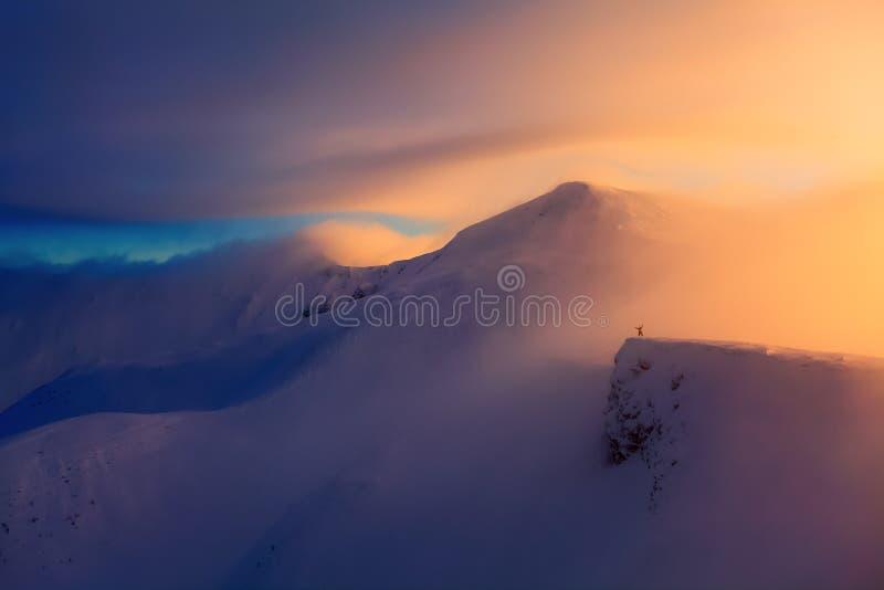 Paesaggio fantastico con un freerider e un alpinista, alte montagne in neve e la nebbia con colore interessante dal sole immagine stock libera da diritti