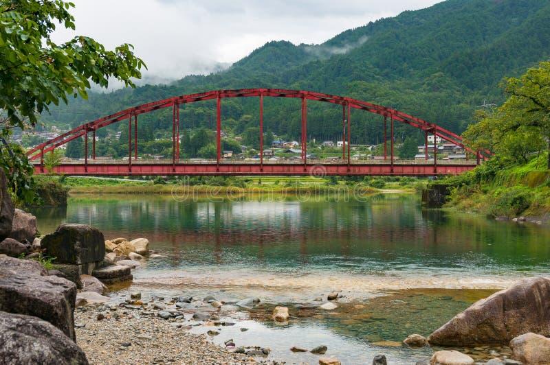 Paesaggio giapponese della campagna con il ponte rosso luminoso sopra Kiso immagini stock libere da diritti