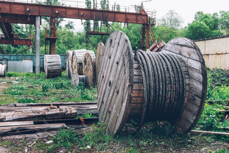 Paesaggio industriale, bobine di cavo d'acciaio arrugginite materiali di legno fotografia stock libera da diritti