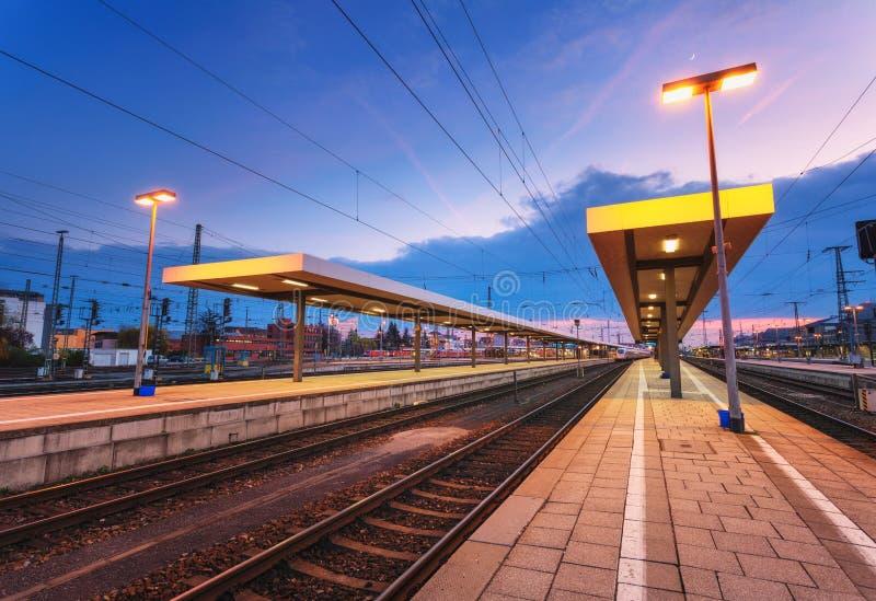 Paesaggio industriale di bella notte, stazione ferroviaria moderna a Norimberga, Germania Piattaforma della ferrovia immagine stock