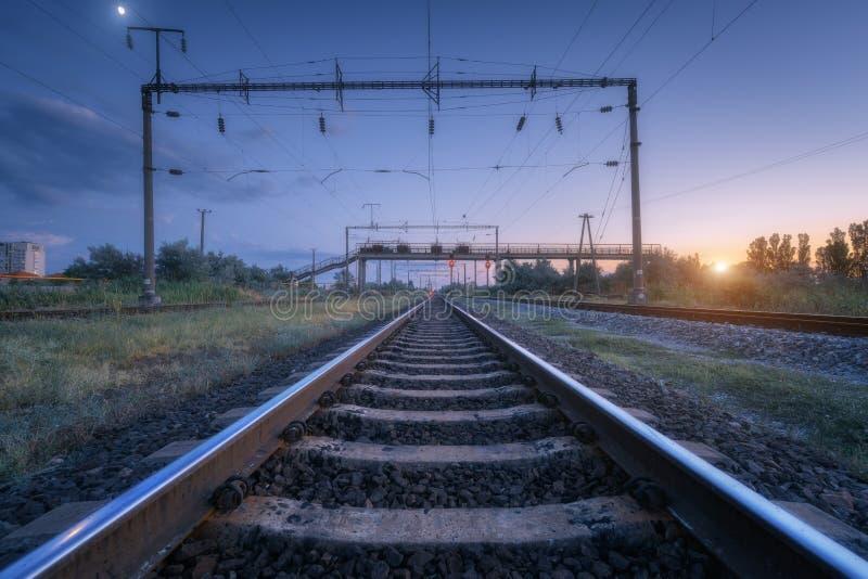 Paesaggio industriale rurale di estate con la stazione ferroviaria al tramonto fotografia stock libera da diritti