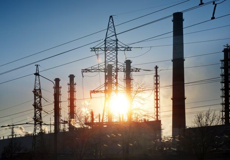 Paesaggio industriale Tramonto sopra la linea elettrica ed i tubi della pianta della cogenerazione immagini stock libere da diritti