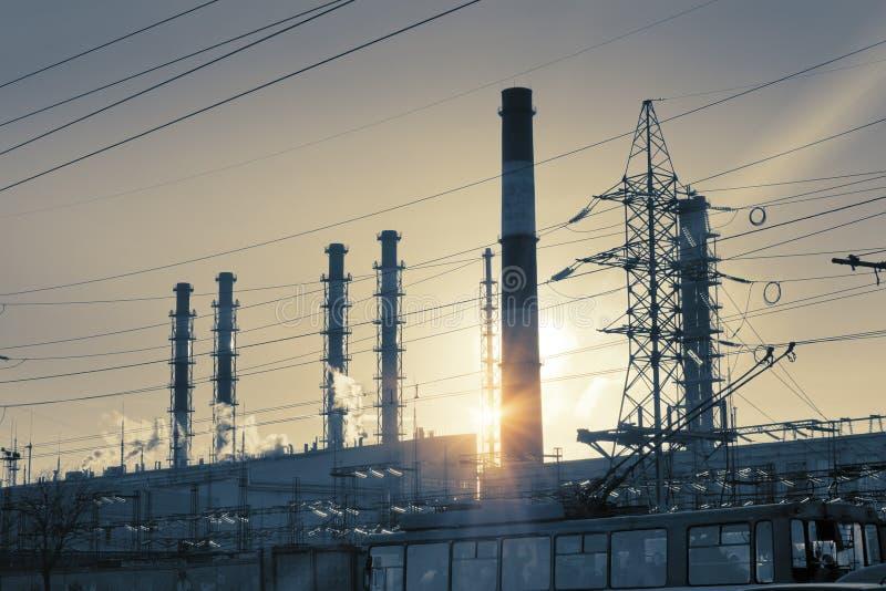Paesaggio industriale Tramonto sopra la linea elettrica ed i tubi della pianta della cogenerazione immagini stock