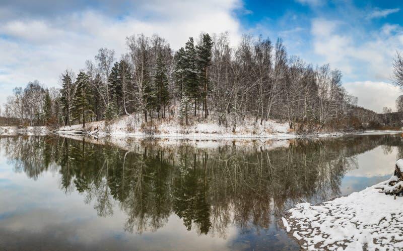 Paesaggio invernale con foresta sul lago, nuvole nel cielo e riflesso fotografia stock