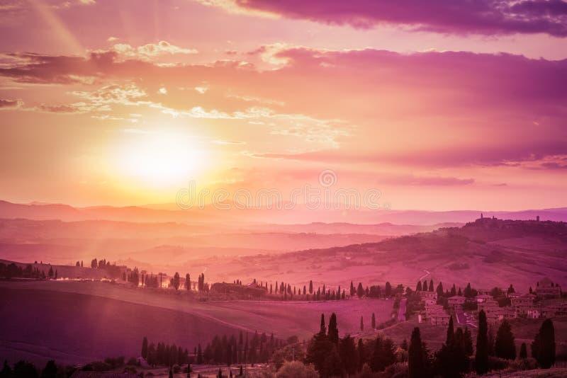Paesaggio meraviglioso della Toscana con gli alberi di cipresso, le aziende agricole e le città medievali, Italia Tramonto rosa e fotografia stock libera da diritti