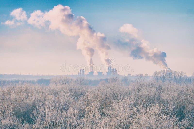 Paesaggio moderno con i tubi della fabbrica alla distanza da cui il fumo sta inquinando l'aria fotografia stock libera da diritti