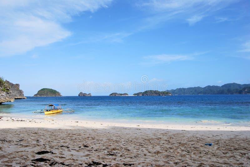 Paesaggio naturale: spiaggia di sabbia tropicale con il mare cristallino e una barca sulla riva fotografia stock