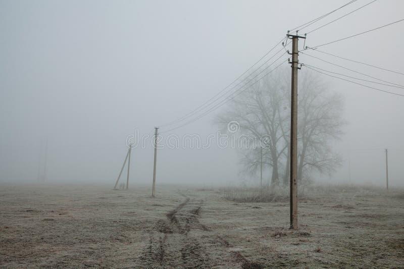 Paesaggio nebbioso con le linee elettriche fondo rustico del campo, gelo sulla terra, effetto del film di rumore immagine stock