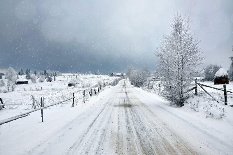 Paesaggio nevoso leggiadramente di inverno con una strada rurale innevata immagini stock