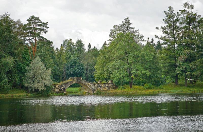 Paesaggio nuvoloso con il ponte medievale in Gatcina fotografia stock libera da diritti