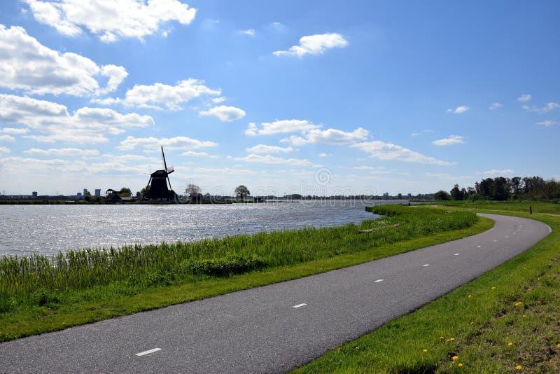Paesaggio olandese con il mulino, il lago e la pista ciclabile immagine stock