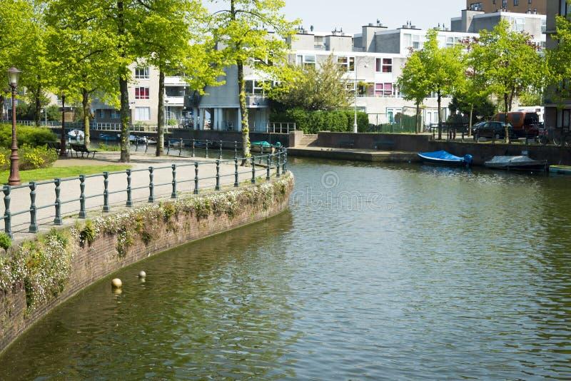 Paesaggio olandese tipico del canale con acqua, gli alberi, l'erba e la barca immagini stock libere da diritti
