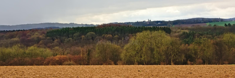 Paesaggio panoramico delle Ardenne, con il terreno coltivabile di inverno e foreste e colline vuoti un giorno piovoso con le nuvo immagini stock