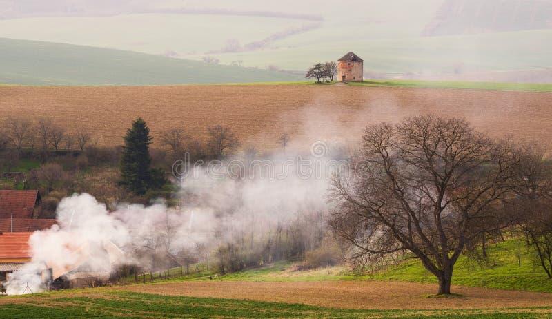 Paesaggio pastorale rurale della primavera con il vecchio mulino a vento senza lame e terra arata su fondo del villaggio e dello  fotografia stock