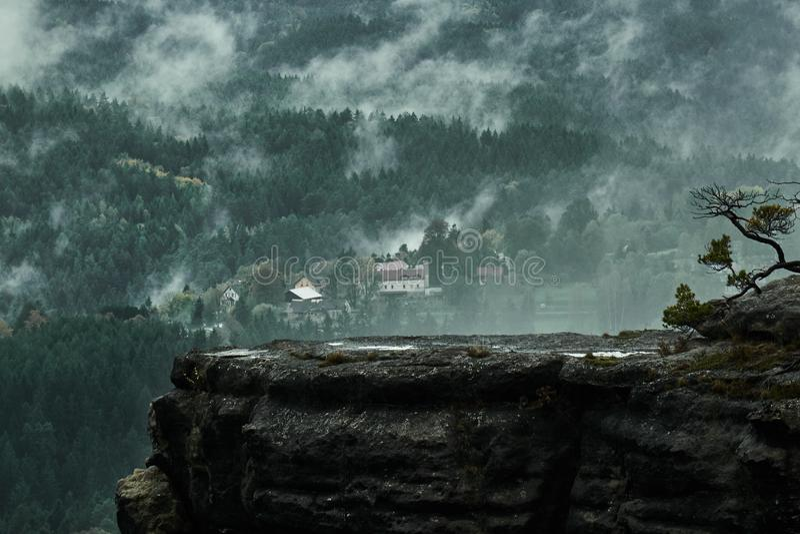 Paesaggio piovoso nebbioso scuro impassibile di mattina con i montains rocciosi della sabbia in Ceco Saxon Svizzera nei colori di fotografia stock libera da diritti