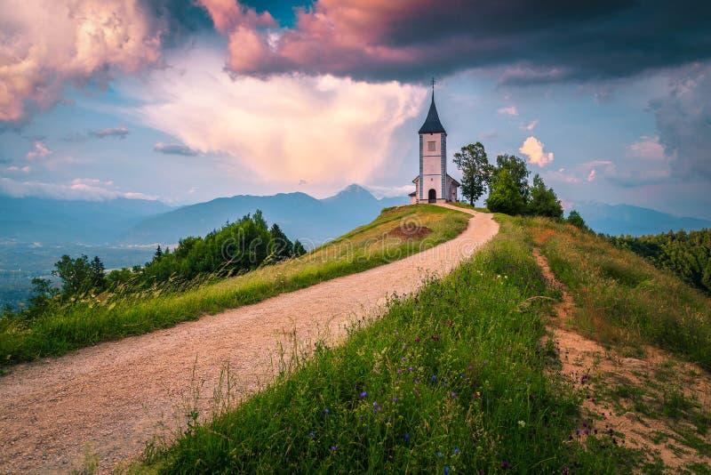 Paesaggio pittoresco alpino con la chiesa di Saint Primoz, vicino a Jamnik, Slovenia fotografia stock