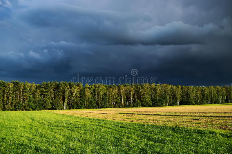 Paesaggio rurale con il cielo drammatico scuro dopo la tempesta di pioggia di estate immagine stock