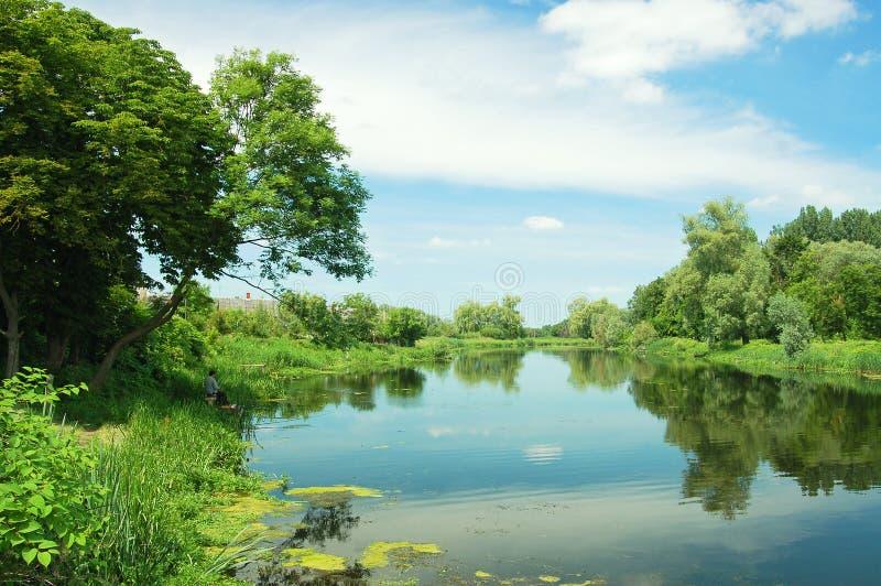 Paesaggio rurale con il pescatore, cielo blu fotografia stock