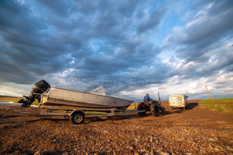 Paesaggio rurale con l'automobile, il trattore e la barca in villaggio yakutian, Yakutia, Russia fotografia stock libera da diritti