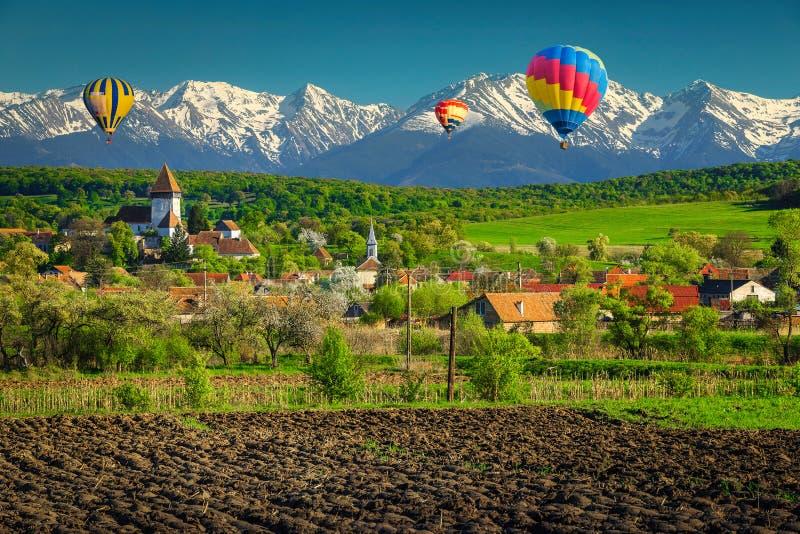 Paesaggio rurale con villaggio Hosman e palloni per l'aria calda, Romania fotografia stock