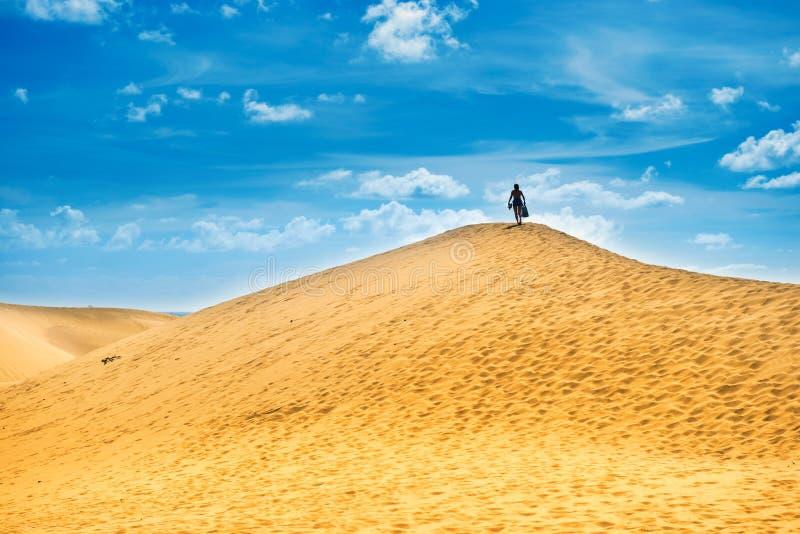 Paesaggio sabbioso con la donna sopra la duna fotografia stock