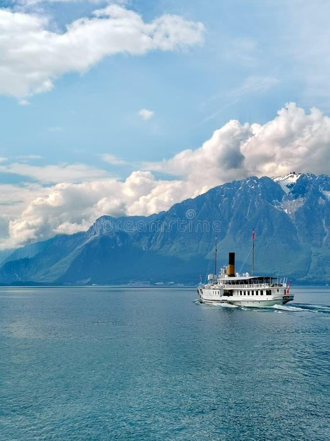 Paesaggio sopra il lago Lemano con una barca e il Grammont come fondo in Svizzera fotografia stock