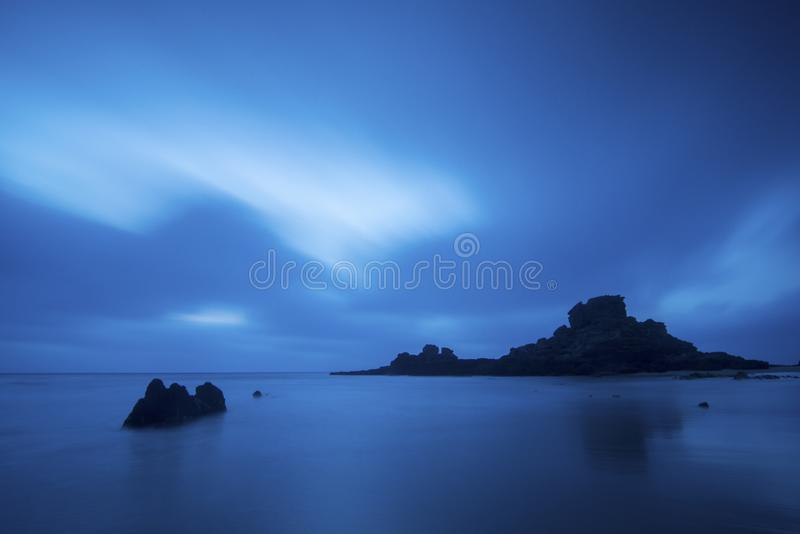 Paesaggio stupefacente dell'oceano notte e nuvole e nebbia del lige dell'acqua Rocce in mezzo al mare esposizione lunga con le nu fotografia stock libera da diritti