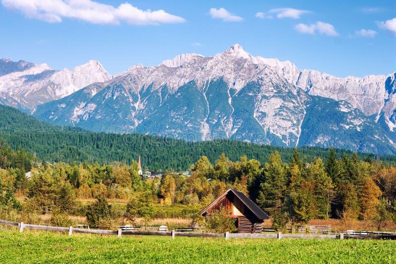 Paesaggio tirolese idilliaco con le colline, la foresta, la casa dell'azienda agricola ed i campi verdi immagini stock