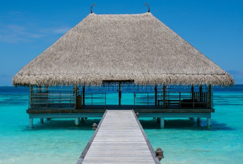Paesaggio tropicale della spiaggia con il ponte di legno e casa sull'acqua alle Maldive immagine stock libera da diritti