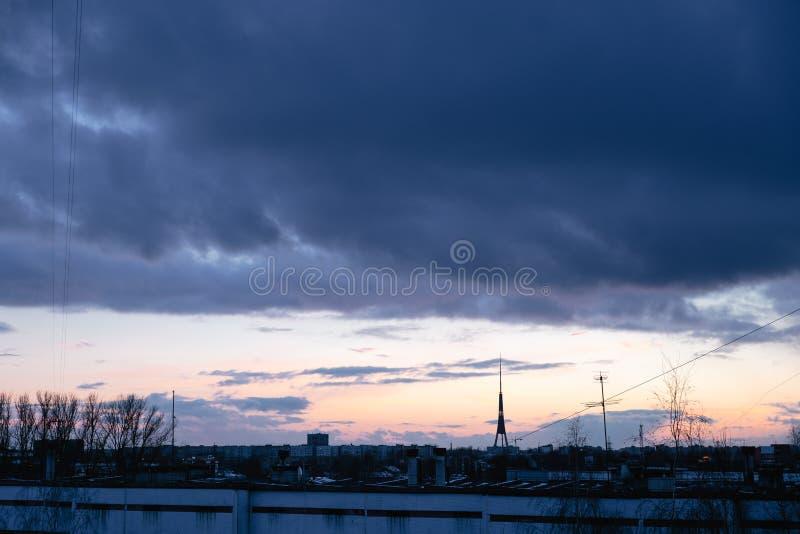 Paesaggio urbano con l'alba viva varicolored meravigliosa Cielo blu drammatico di stupore con le nuvole porpora e viola sopra bui fotografia stock