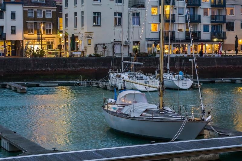 Paesaggio urbano dei bacini di Vlissingen, barca decorata con le luci, città popolare in Zelandia alla notte, Paesi Bassi immagine stock