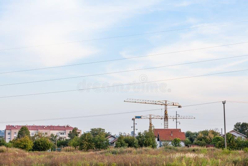 Paesaggio urbano dei peri del sobborgo di Belgrado, con le gru su un cantiere in mezzo ai campi fotografia stock libera da diritti