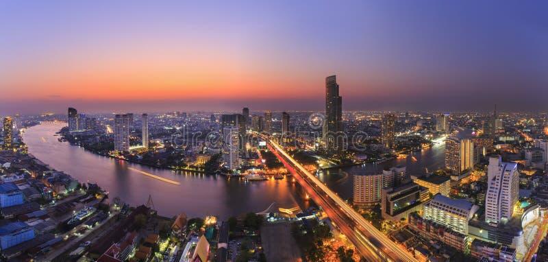 Paesaggio urbano del fiume nella città di Bangkok con la costruzione dell'alta carica nella notte fotografie stock