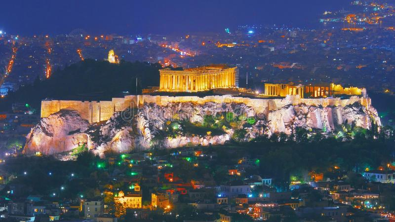 Paesaggio urbano di Atene con la collina illuminata dell'acropoli, Pathenon e costruzione e mare di Herodium alla notte Orizzonte fotografia stock libera da diritti