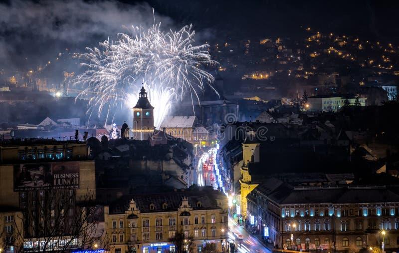 Paesaggio urbano di Brasov di notte la vigilia dei nuovi anni con i fuochi d'artificio fotografia stock libera da diritti