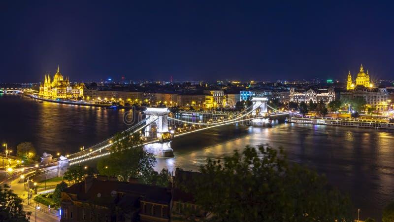 Paesaggio urbano di Budapest con la basilica di St Stephen, il ponte a catena ed il Parlamento ungherese alla notte, Ungheria immagini stock libere da diritti