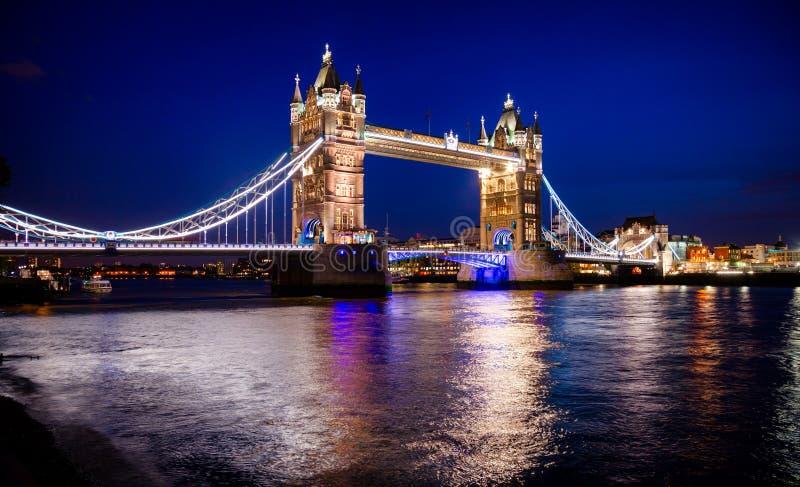 Paesaggio urbano di Londra con il ponte illuminato della torre sopra il Th del fiume fotografia stock libera da diritti