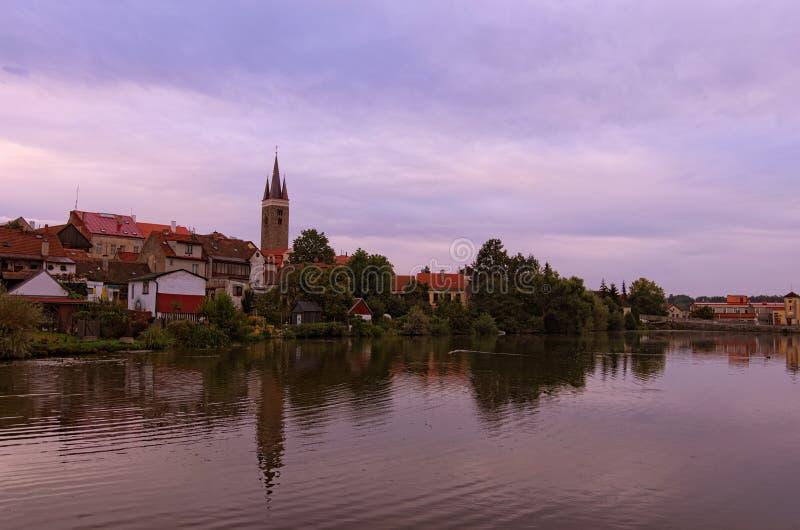 Paesaggio urbano di mattina di Telc medievale La torre della chiesa dello Spirito Santo in Telc ha riflesso nell'acqua del lago d fotografia stock