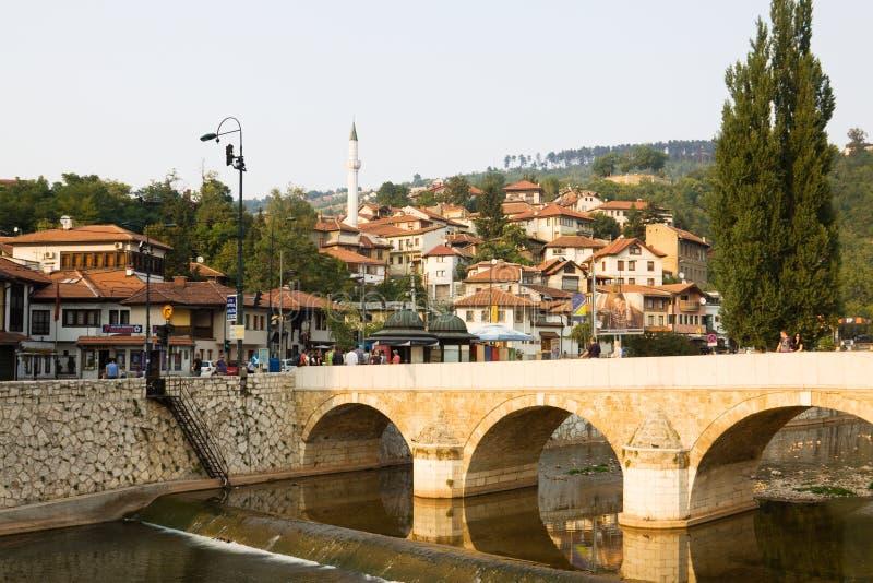 Paesaggio urbano di Sarajevo con il fiume di Miljacka e un ponte immagini stock