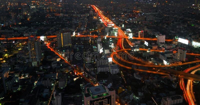 Paesaggio urbano futuristico di notte con traffico attraverso la via Bangkok, Tailandia immagini stock