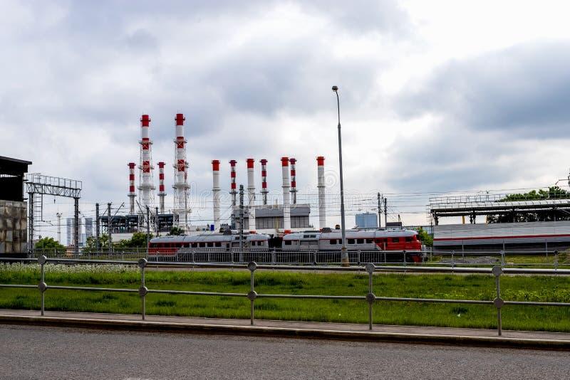 Paesaggio urbano industriale Treno e fumaioli nei precedenti di un cielo tempestoso fotografia stock